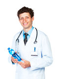 Portrait of a smiling male doctor holding bottle of water on whi Royalty Free Stock Images