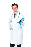 Portrait of a smiling male doctor holding bottle of water on whi Stock Images