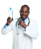 Portrait of a smiling male doctor holding bottle of water on whi Royalty Free Stock Image