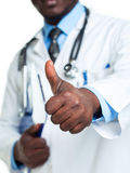Portrait of a smiling male doctor holding a notepad and finger u Royalty Free Stock Image