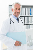 Portrait of a smiling male doctor at medical office Stock Photos