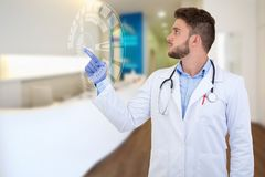 Portrait of a smiling male doctor pointing finger away with tech illustration. Royalty Free Stock Photography