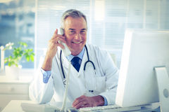 Portrait of smiling male doctor using telephone in clinic Royalty Free Stock Photography