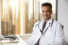 Portrait Of Smiling Male Doctor Wearing White Coat With Stethoscope In Hospital Office royalty free stock photography