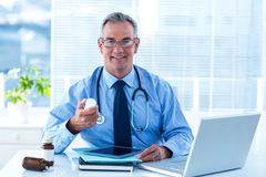 Portrait of smiling male doctro with pill bottle in hospital Royalty Free Stock Images