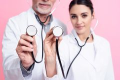 Portrait of smiling male and female doctors holding stethoscopes to camera isolated. Portrait of smiling male and female doctors in white gowns holding Royalty Free Stock Photography