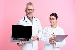 Portrait of smiling male and female doctors with stethoscopes holding laptop and clipboard . Portrait of smiling male and female doctors in white gowns with Stock Photography