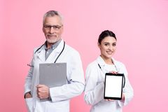 Portrait of smiling male and female doctors with stethoscopes holding tablet and clipboard isolated. Portrait of smiling male and female doctors in white gowns Stock Photos