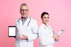 Portrait of smiling male and female doctors with stethoscopes holding tablet and clipboard isolated. Portrait of smiling male and female doctors in white gowns Stock Image