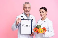 Portrait of smiling male and female doctors with stethoscopes holding diet sign and plate of vegetables isolated. Portrait of smiling male and female doctors in Royalty Free Stock Photos