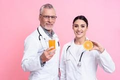 Portrait of smiling male and female doctors with stethoscopes holding juice and orange isolated. Portrait of smiling male and female doctors in white gowns with Royalty Free Stock Photos