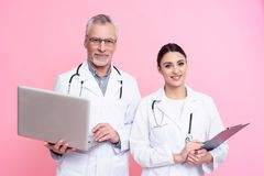 Portrait of smiling male and female doctors with stethoscopes holding laptop and clipboard isolated. stock photo