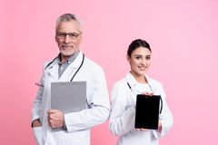 Portrait of smiling male and female doctors with stethoscopes holding tablet and clipboard isolated. Portrait of smiling male and female doctors in white gowns Royalty Free Stock Photography