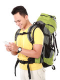 Portrait of a smiling male hiker with backpack using mobile phon Stock Images