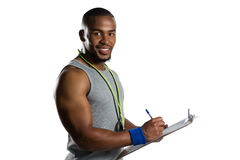 Portrait of smiling male rugby coach writing on clipboard. While standing against white background Royalty Free Stock Images