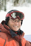 Portrait of Smiling Male Skier. Smiling male skier wearing red goggles and orange ski jacket. Vertical shot Stock Images