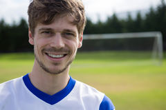 Portrait of smiling male soccer player. With arms crossed standing on playing field Royalty Free Stock Images