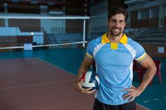 Portrait of smiling sportsperson holding volleyball Royalty Free Stock Images