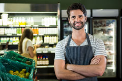 Portrait of smiling male staff standing with arms crossed in organic section Royalty Free Stock Images