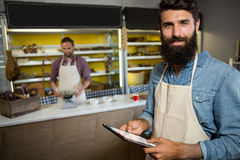 Portrait of smiling male staff using digital tablet near counter. In shop Stock Images
