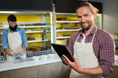Portrait of smiling male staff using digital tablet near meat counter. In market Royalty Free Stock Photo