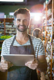Portrait of smiling male staff using a digital tablet in organic section. Of super market Royalty Free Stock Photography