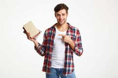 Portrait of a smiling male student holding books. And pointing finger  over white background Stock Image