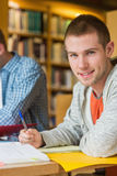 Portrait of a smiling male student at library desk. Portrait of a smiling male student with a friend sitting at desk in the college library Royalty Free Stock Photos