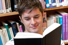 Portrait of a smiling male student reading a book. Sitting on the floor in a bookshop Royalty Free Stock Image