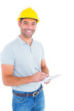 Portrait of smiling male supervisor writing on clipboard Royalty Free Stock Images