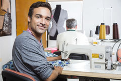 Portrait Of Smiling Male Tailor Using Sewing Machine Stock Photography