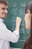Portrait of smiling male teacher with student in front of chalkboard writing Royalty Free Stock Photos