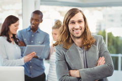 Portrait of smiling man with arms crossed while coworkers discussing Royalty Free Stock Photography