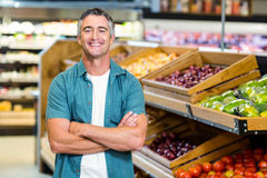 Portrait of a smiling man with arms crossed. At supermarket Stock Photo