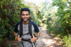 Portrait of smiling man with backpack walking in the forest Royalty Free Stock Photo