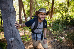 Portrait of smiling man with backpack walking in the forest Stock Photo
