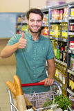 Portrait of smiling man buy products with his trollet and thumb up Stock Photos