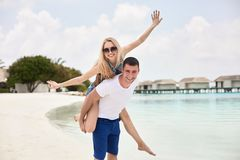 Portrait of smiling man carrying woman on his back along the sea shore. Guy giving piggyback ride to girlfriend by ocean royalty free stock photography