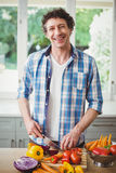 Portrait of smiling man cutting vegetables at home Stock Photo