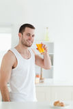 Portrait of a smiling man drinking orange juice. In his kitchen Stock Photos