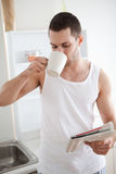 Portrait of a smiling man drinking tea while reading the news Royalty Free Stock Image
