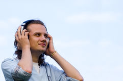 Portrait of a smiling man with earphones. With sky behind stock images