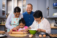 Portrait of smiling man with family preparing food in kitchen Royalty Free Stock Photo