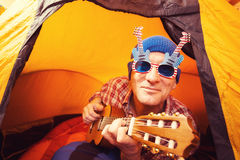 Portrait of smiling man in the funny glasses with ukulele Royalty Free Stock Photos