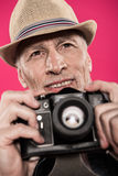 Portrait of smiling man in hat holding photo camera and looking away Stock Image
