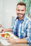 Portrait of smiling man having food Stock Photo