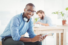 Portrait of smiling man with headphones while using digital tablet Royalty Free Stock Photography