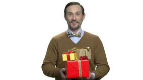 Portrait of smiling man hoding gift boxes.