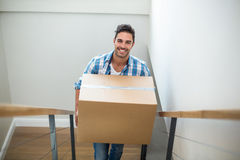 Portrait of smiling man holding cardboard box while climbing steps Royalty Free Stock Photos
