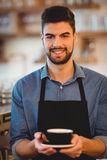 Portrait of smiling man holding cup of coffee. In office cafeteria Stock Image